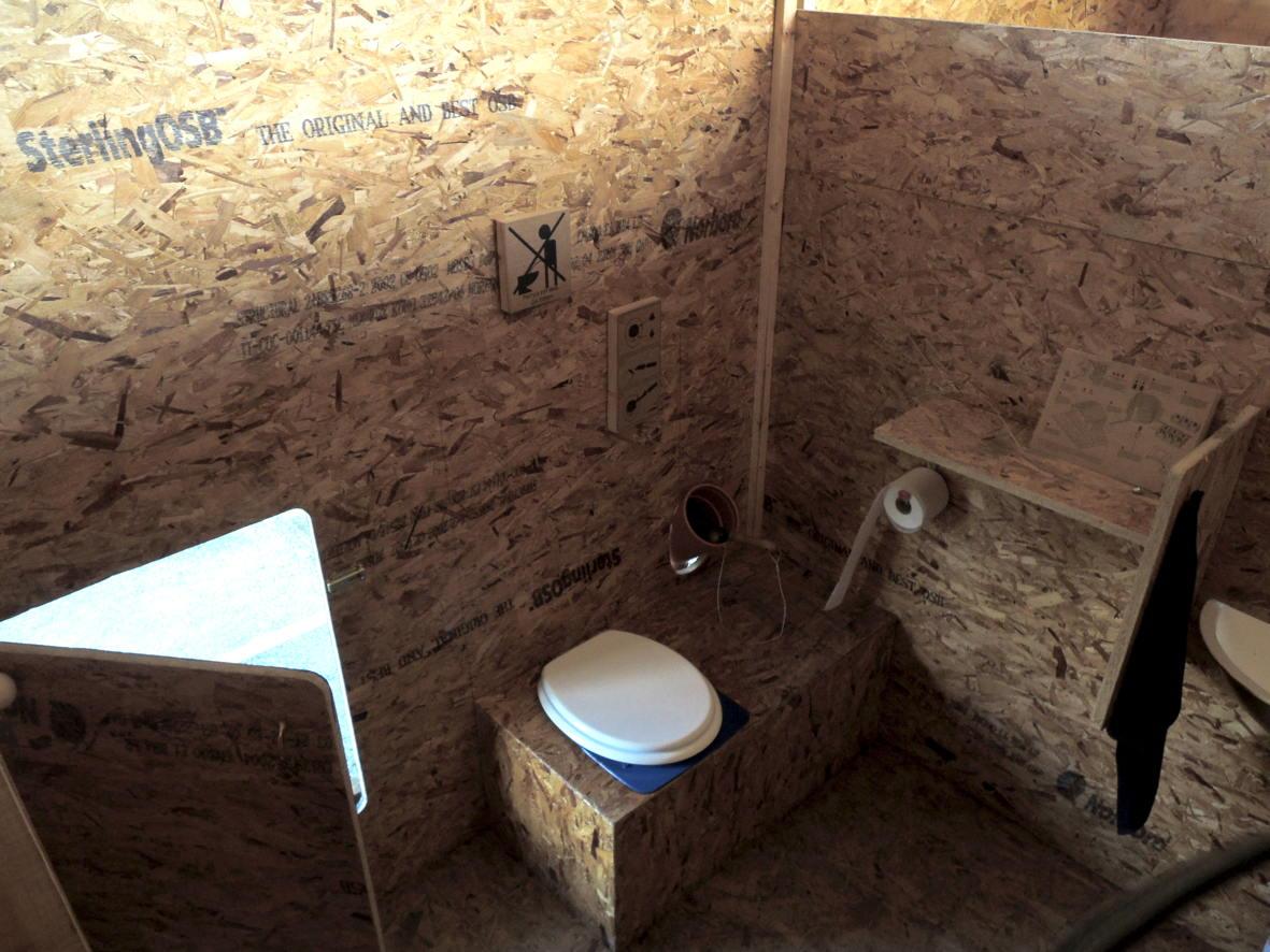 Rechts neben der Toilette ist der Behälter mit dem Terra Preta Streu, links der Ausgang für Kinder, die Rutsche.