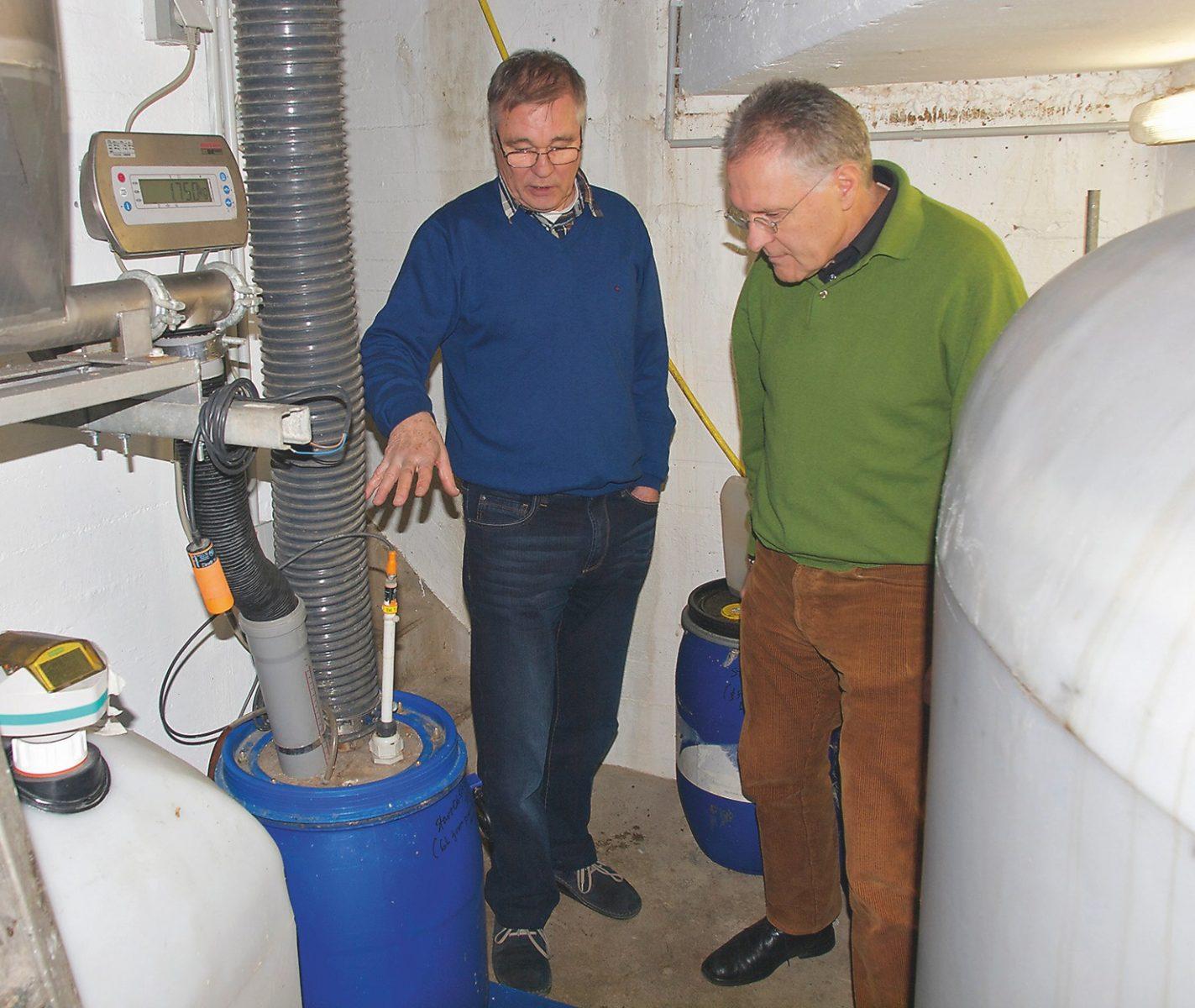 Peter-Nils Grönwall erklärt Pit Mau die automatische Verarbeitung der Feces. Pro 300 g werden eine Lage Biokohle und einige Sprühstöße EM zugeführt.