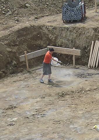 EM-Keramikpulver wird auf den Boden der Baugrube verteilt.