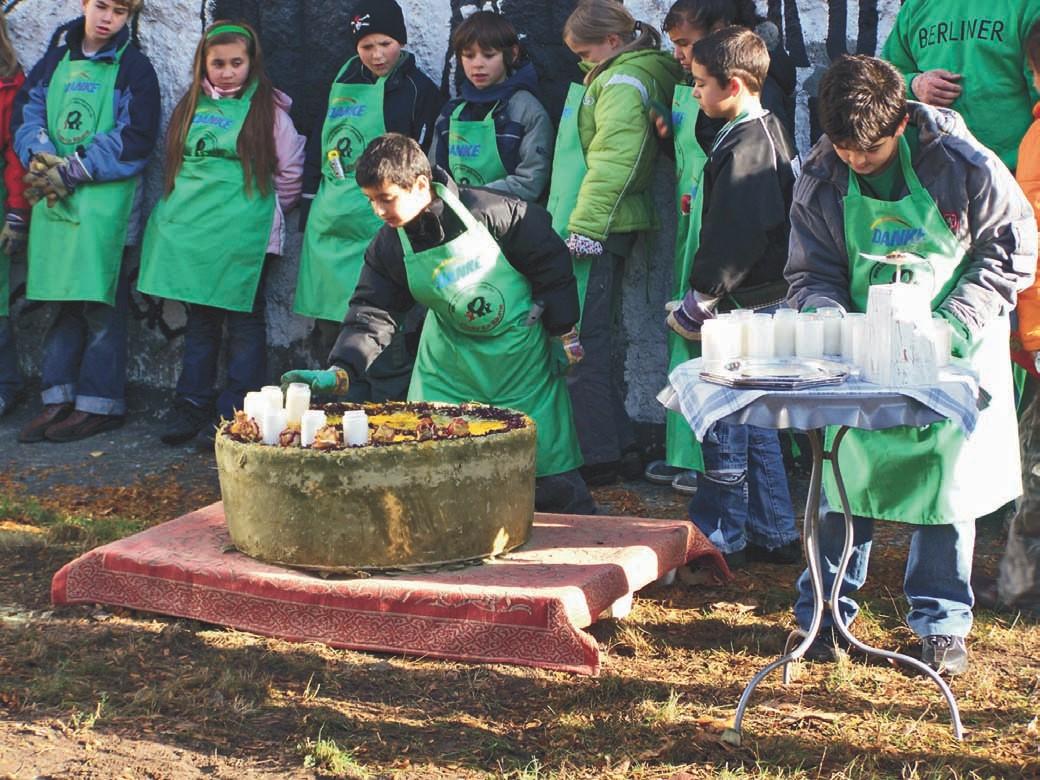 Die Kinder der Regenbogen- Grundschule dekorieren die Bokashi-Torte, die sie anschließend den Bäumen zum Jubiläum an die Wurzeln geben.