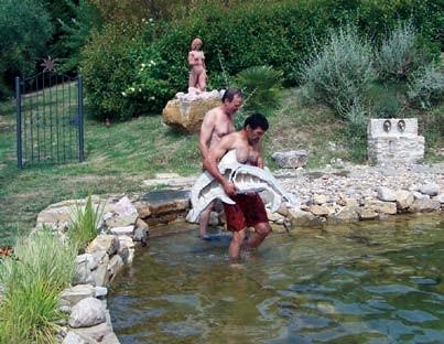 Antonio Dema trägt eine Figur ins Wasser