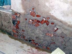 Löcher werden gestopf, indem tiefere Unebenheiten mit Ziegelsteinstückchen gefüllt werden.